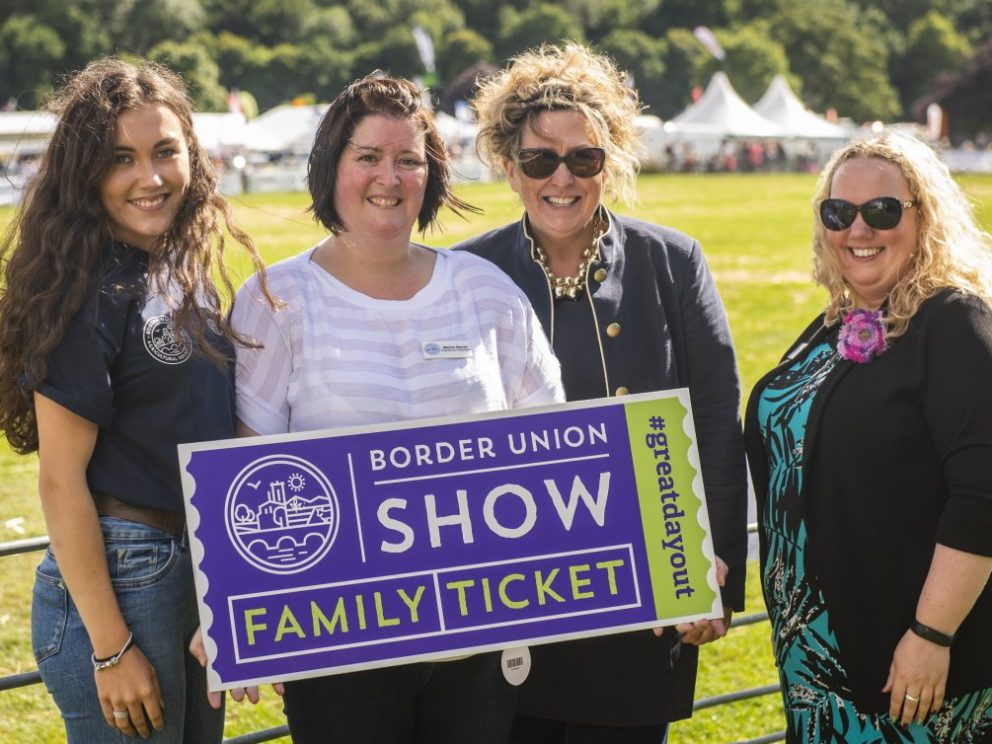 4 ladies holding a sign advertising the Border Union Show in Kelso